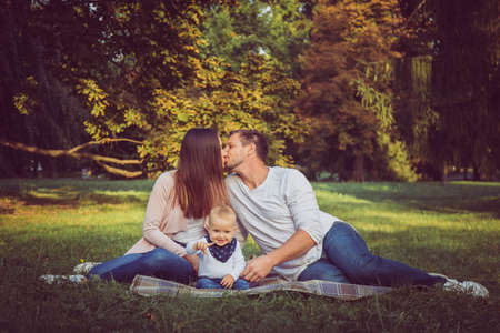 A happy family on a picnic. Infant, mother and father in outside in nature.
