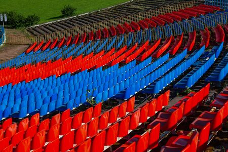 The stands of the old football stadium with rows of plastic seats in red and blue 版權商用圖片