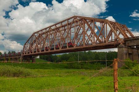 Suburban train rides on a high old iron bridge with concrete piers Stok Fotoğraf