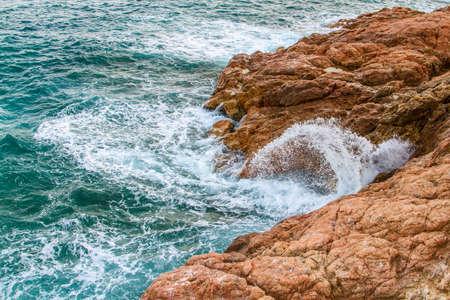 Sea waves with splashes crash on the coastal stones