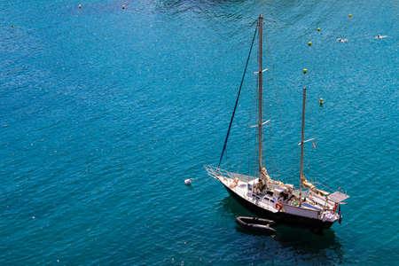Two-masted sailing yacht anchored at sea.
