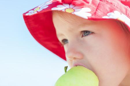 child girl eating big green apple closeup outdoor Standard-Bild