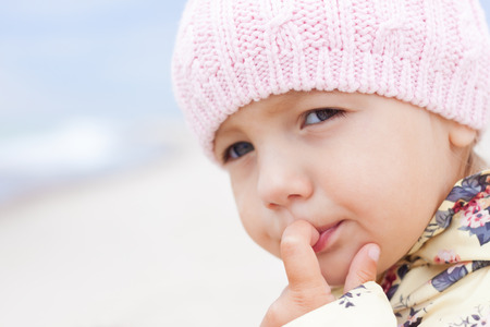 child girl looking thinking with finger at mouth