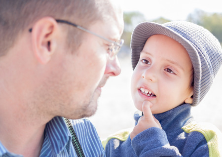 son and father looking each other eyes closeup outdoor