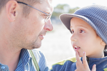 son father look each other talk closeup outdoor