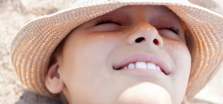 smile close up: summer vacation child face happy smile close up straw hat outdoor Stock Photo
