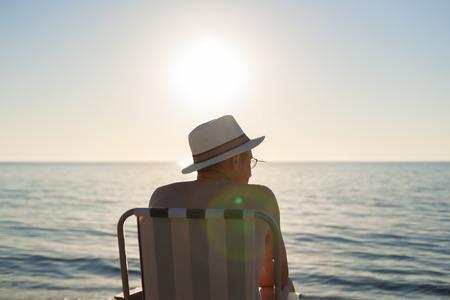 남자 앉아 일몰 해변 백라이트 렌즈 플레어 선택적 포커스