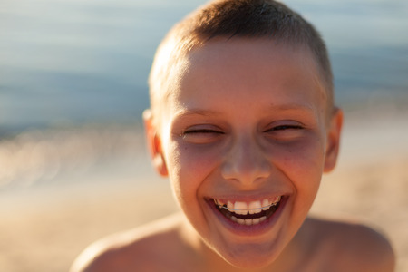 child looking up: child boy portrait close up sunset backlight happy laughing braces teeth selective focus Stock Photo