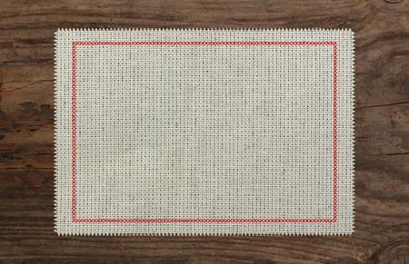 cloth table edge fabric torn, red stich cross border Standard-Bild