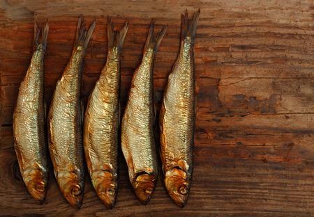 herring sprat fish smoked wooden table Standard-Bild