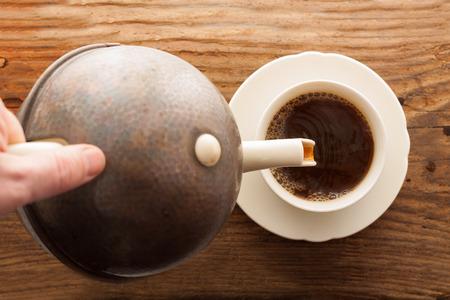 tea pour cup pot wooden table hand top view Standard-Bild