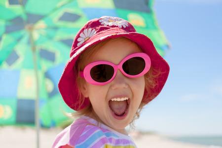 Kind glücklich Lächeln gesunde Zähne Sonnenbrille Strand Sommerferien Standard-Bild