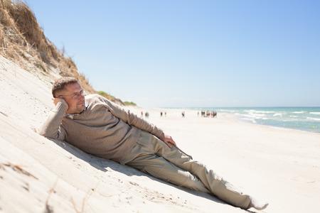 남자 45 세 편안한 해변 거짓말 모래 언덕