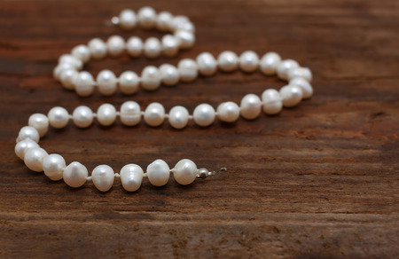 string of pearls: pearls string wooden table closeup shallow DOF