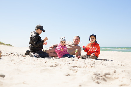 beach family lying on sand and play, father of many children, kids blowing bubbles