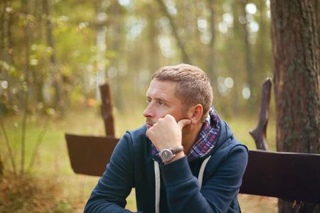 秋の公園、選択と集中で座っている男思考不機嫌そうな肖像