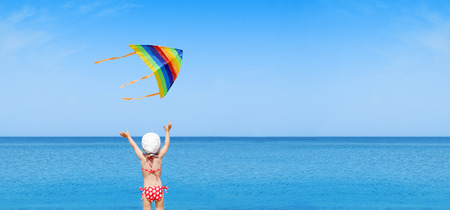 healthy girl: panorama child play flying kite on beach Stock Photo