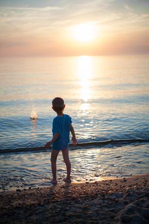 해변 일몰 백라이트 자식 소년은 돌을 던져