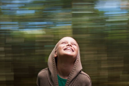 10 to 12 years old: chid happy laughing nature movement background, shallow DOF