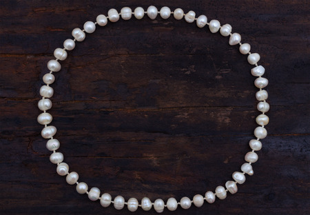 string of pearls: pearls string circle shaped top view old wood background Stock Photo