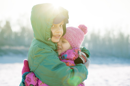 children happy hug backlight playing outside selective focus stylized