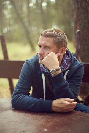 midlife crisis man thinking portrait sitting outside selective focus