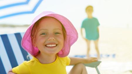 child close up portrait happy smile summer camp sitting chair umbrella selective focus backlight