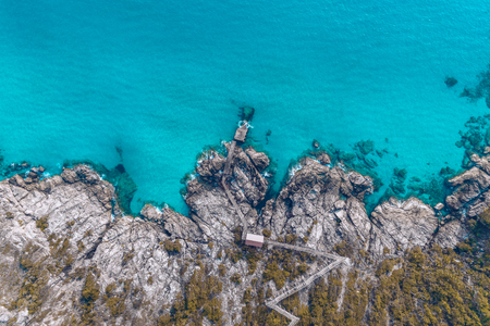 Old Jetty on a Rocky Beach with Blue Water at Perhentian Islands, Terengganu Stock Photo