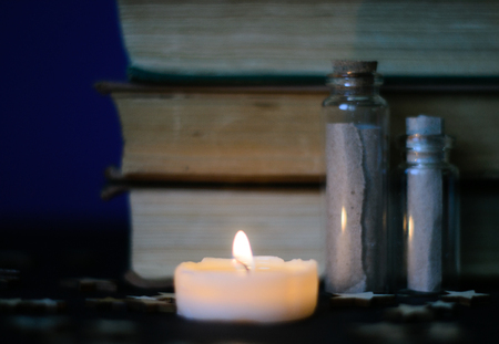 Dark picture with old books, candles and spelljars