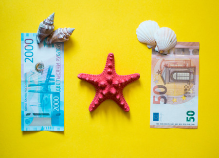 euro and ruble with red and white seashells on yellow backgrong