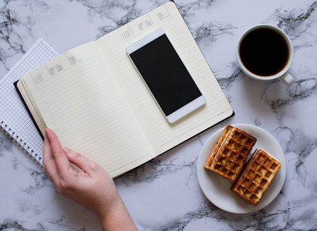 Woman are planning the day, coffee, waffles, marble background Banco de Imagens