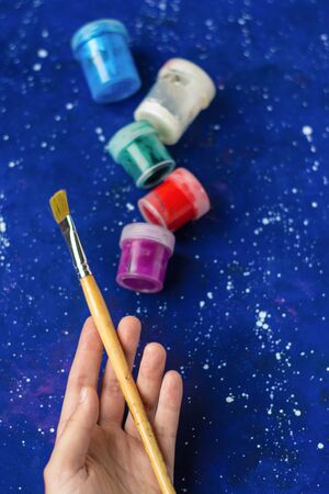 Hand holds brush, jars of different colors paint on galaxy-blue background