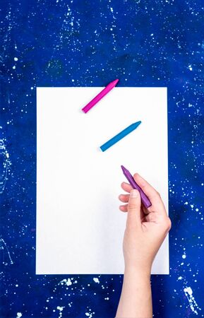 Blank sheet of white paper and hand hold crayons on galaxy-blue background Stok Fotoğraf