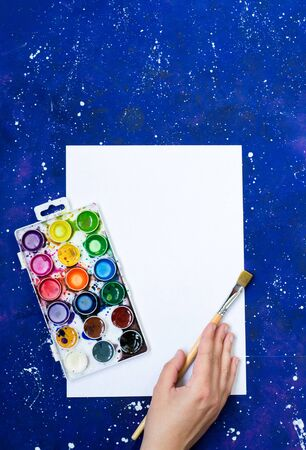 Watercolor palette and paintbrush on blank sheet and blue-space background