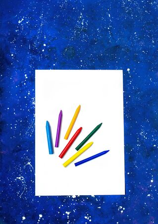 Blank sheet of white paper and multicolor crayons on galaxy-blue background