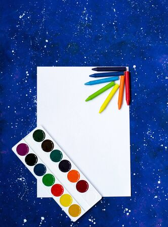 Watercolor palette with crayons on blank whit sheet of paper and space-blue background
