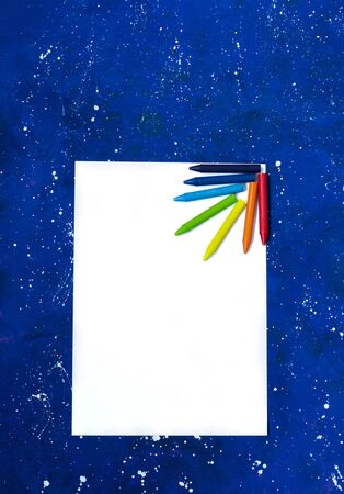 Blank sheet of white paper and crayons on galaxy-blue background