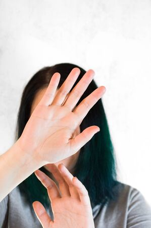 A portrait of unrecognizable young woman with her hands cover her face