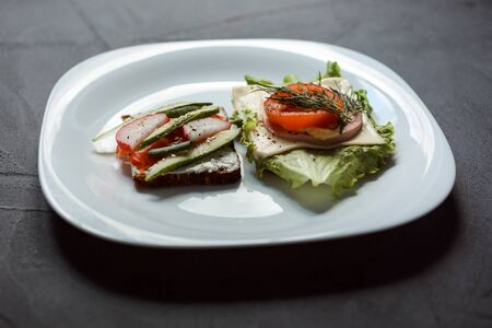 Two delicious sandwiches on the white plate. Grey textured background. Breakfast time. Standard-Bild