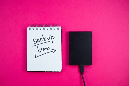 Black hard drive with a Notepad Backup text time is lying on a pink background. View from the top. Backup concept.