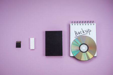 history of data storage devices on a lilac background. dvd, flash drive, hard drive, sd card top view. Notepad backup text Reklamní fotografie