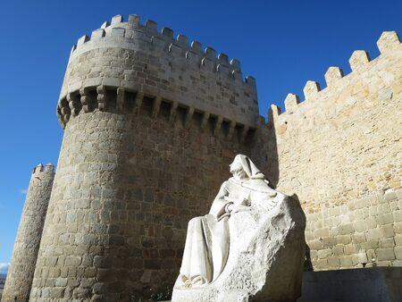 The city wall of Avila near Alcazar Gate (Puerta del Alcazar) with the statue of Santa Teresa in Avila, SPAIN Editorial