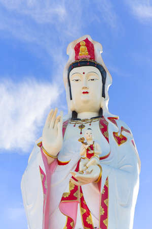 Statue of Godness Guan Yin in Thailand with blue sky background photo