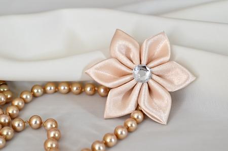kanzashi: Handmade kanzashi flower and pearls on white background Stock Photo
