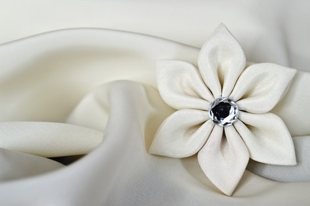 kanzashi: Handmade silk fabric flower on satin background