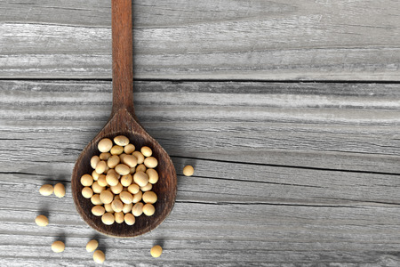 Soybeans in wooden spoon Imagens