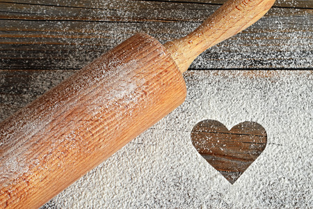 Heart, flour and rolling pin on wooden background Stock Photo