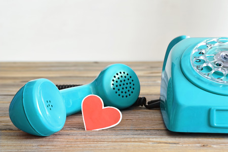 telephone receiver: Fathers Day card: Old blue telephone and heart  shaped tag on wooden background Stock Photo