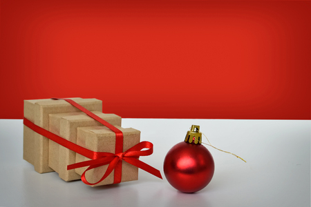 tied together: Three Christmas gift boxes tied together with red ribbon and red bauble