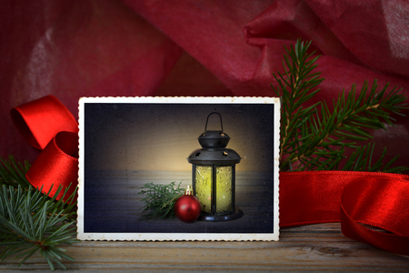 Christmas card: lantern, christmas ball and spruce branch on vintage photo